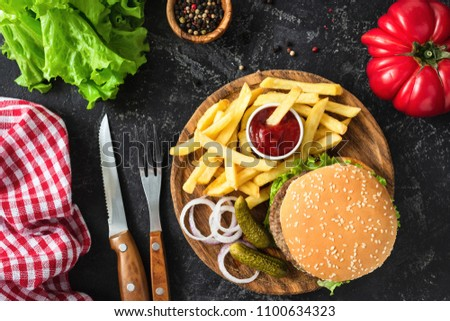 Beef burger with lettuce and tomato, potato fries and ketchup on dark background. Table top view. Fast food, unhealthy eating concept