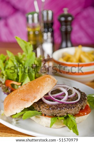Beef burger with salad and a side dish of fries