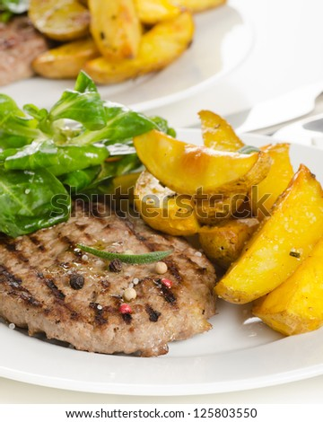 Beef burger with the roasted potato, side salad and spices on white plate
