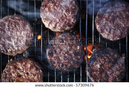 beef burgers cooking on a BBQ