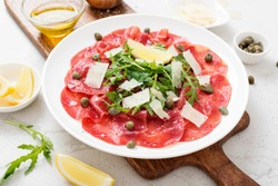 Beef Carpaccio cold appetizer with parmesan, capers and arugula on white plate.