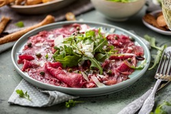 Beef carpaccio on black plate with mustard and parmesan