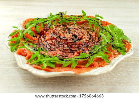 Beef carpaccio with arugula and balsamic souce on white plate on rustic table background. Side view. Selective soft focus. Shallow depth of field. Text copy space. Close up. Stock foto ©