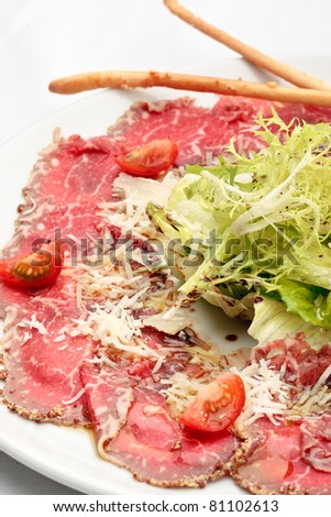 Beef carpaccio with lettuce, tomatoes and parmesan on a white plate - stock photo