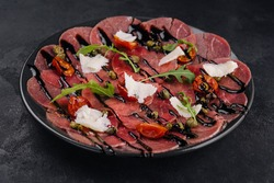 Beef carpaccio with parmesan, dried tomatoes and capers on a black plate on a black texture background