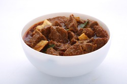 Beef curry_Kottayam style beef curry garnished with fried coconut slices and curry leaves_south Indian style arranged in awhite bowl with white background