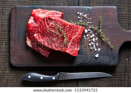 Beef cut: raw flat iron steaks of corn-fed cows on a dark wooden cutting board on a dark wooden background with fresh rosemary, sea salt, olive oil, peppercorns, garlic, view from above ストックフォト ©