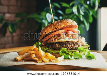 Beef Egg and Bacon Burger Served in Restaurant. American Food. Tasty Gourmet on Wooden Table.
