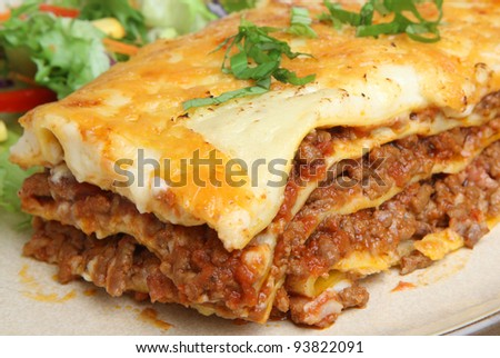 Beef lasagna with salad. Shallow DoF, focus to the right of image center.