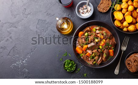 Beef meat and vegetables stew in black bowl with roasted baby potatoes. Dark background. Copy space. Top view.