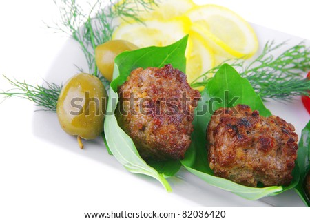 beef meat cutlet with tomatoes on long white plate