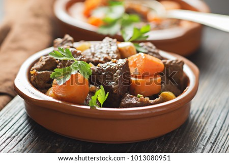Beef meat stewed with carrots and spices in ceramic pot  on old black wooden board. Selective focus.