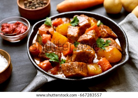 Beef meat stewed with potatoes and carrots in cast iron pan, close up view.