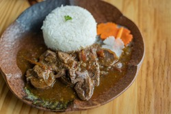 Beef meat stewed with rice and carrots in brown ceramic dish on wooden table beautiful texture background. Top view or flat lay style.