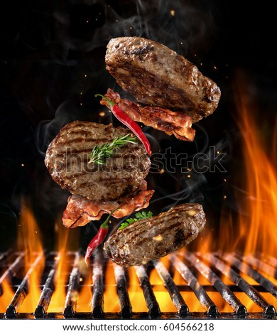 Beef milled meat on hamburger with chilli peppers and bacon, flying above grill with flames on black background #604566218