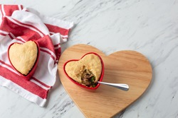 Beef Pot Pies in Red Heart-Shaped Dishes; One with Spoon; On Heart-Shaped Board on White Counter Top