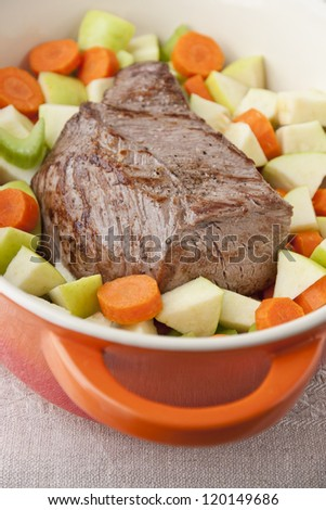 Beef Roast prepared with carrots, apples and  celery  in french oven. selective focus, shallow dof