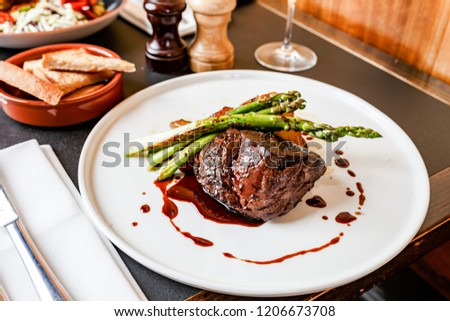 Beef rump on a white plate with red wine sauce and asparagus on a dark table. #1206673708