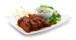 Beef Satay (Sate Daging) Indonesia Food Appetizer Easy dish Style Served Chili Sauce and Chilli and cucumber in vinegar sauce decorate carved vegetables sideview