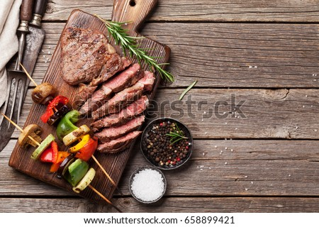 Beef steak and grilled vegetables on cutting board on wooden table. Top view with copy space