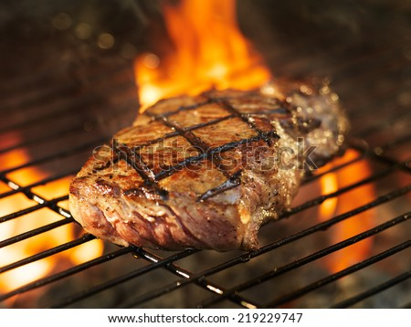 beef steak cooking over flaming grill #219229747