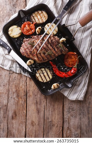 beef steak grilled with onions and eggplant in the pan grill. Vertical view from above