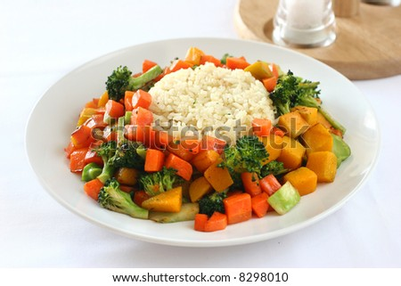 Beef steak on garlic and ginger flavored rice surrounded by mixed vegetables - stock photo