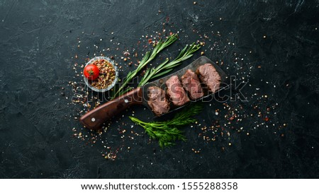 Beef steak on knife, on black stone background. Top view. Free space for your text.