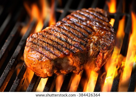 Beef steak on the grill with flames #384426364