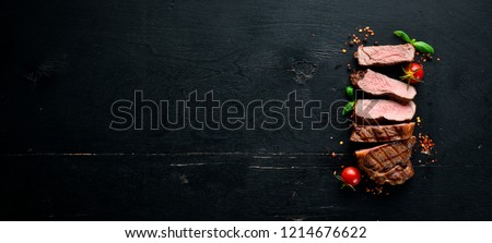 Beef steak. Veal, meat. On a black wooden background. Top view. Free copy space.