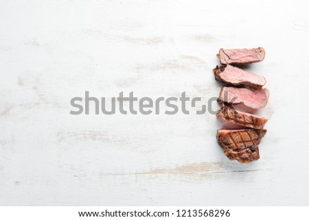 Beef steak. Veal, meat. On a white wooden background. Top view. Free copy space.