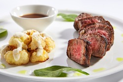 Beef steak with cauliflower dish top view. Baked meat alternative cuts with peppercorn sauce. Roasted pork piece isolated on white background. Gourmet meal garnished with herbs on plate composition