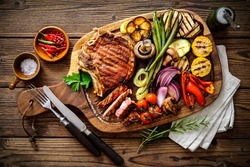 Beef steak with grilled vegetables and seasoning on serving board block