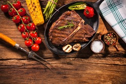 Beef steak with grilled vegetables and seasoning on wooden table