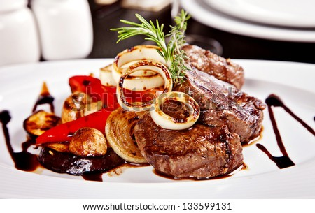 Beef steak with vegetables, rosemary and soy sause served on white plate in restaurant