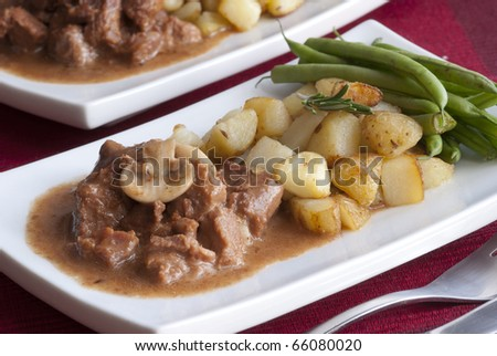 Beef steaks in Italian sauce with roasted potatoes, green beans and rosemary