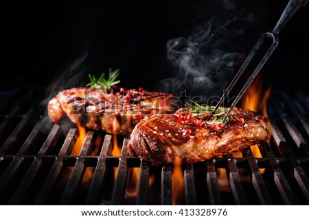 Beef steaks on the grill with flames #413328976