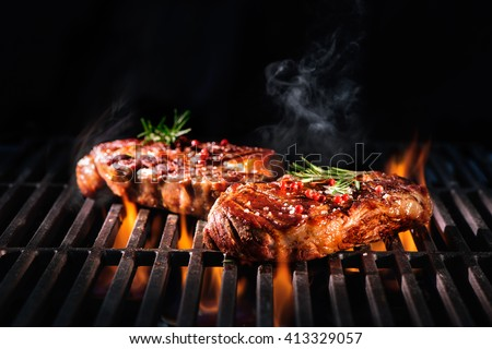 Beef steaks on the grill with flames #413329057