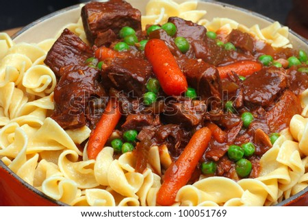 Beef Stew with Carrots & Peas. Close up of beef stew in dutch oven made with top round, baby carrots, green peas & served over a bed of egg noodles.
