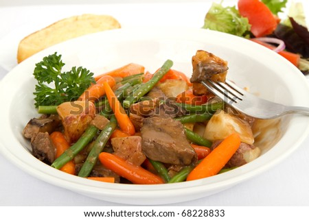 Beef stew with vegetables, a side salad and bread