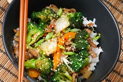 Beef Stir-Fry with broccoli, carrots, onions, peppers, sesame seeds, and ginger on rice