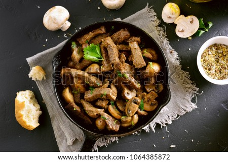 Beef stroganoff with mushrooms in frying pan on black stone background. Top view, flat lay