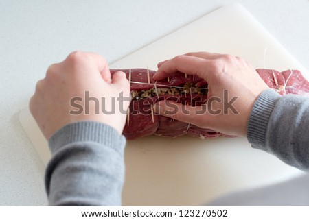 beef stuffed with mushroom filling being laced using a string between the toothpicks