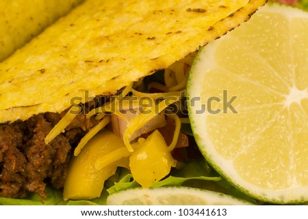 Beef Tacos - Mexican minced beef hard-shell tacos with salsa, cheese and lime. Close up.