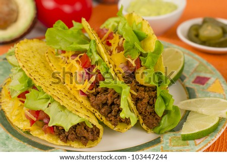Beef Tacos - Mexican minced beef hard-shell tacos with salsa, cheese and lime wedges on a colourful plate. Guacamole and pickled jalapenos chilies on background.