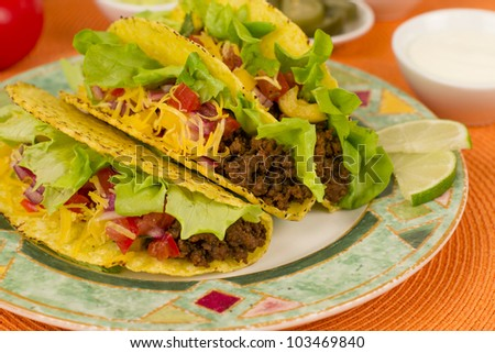 Beef Tacos - Mexican minced beef hard-shell tacos with salsa, cheese and lime wedges on a colourful plate. Sour cream and pickled jalapenos chilies on background.