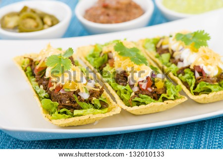 Beef Tacos - Shredded beef taco trays topped with salsa, sour cream and grated cheese. Refried beans, guacamole and jalape�±os in background