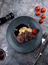 Beef tenderloin medallions with mulled wine sauce with grilled vegetables on black plate