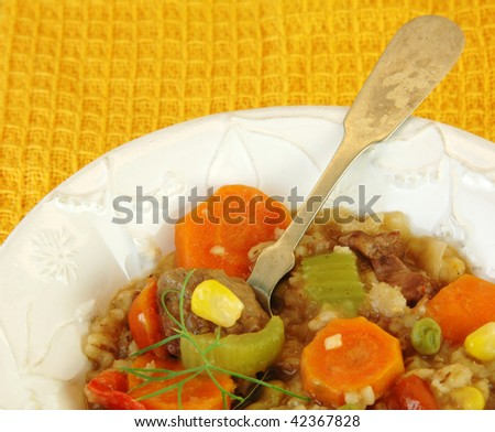 Beef vegetable stew close up with a yellow background.