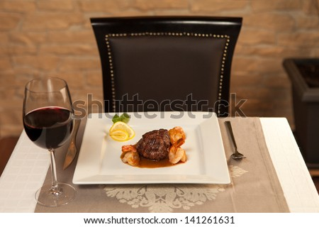 Beef with shrimp and red wine on table